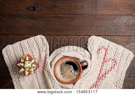 Christmas background. Coffee cup knitting scarf present gift box and candy canes on wooden background. Holidays card. Top view