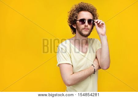 Portrait of curly-haired young man in sunglasses and bermudas looking confused at camera. Isolate. Yellow background.