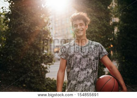 Portrait of handsome young basketball player holding a ball on outdoor court. Smiling teenage streetball player looking at camera.