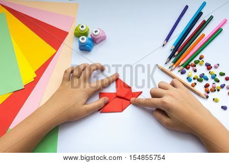 Children's hands do origami bird from red paper. Working place is decorated with leaves of color paper scissors colored wood ladybugs and pencils.