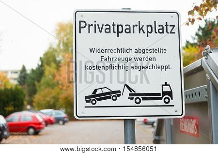 HANNOVER / GERMANY - OCTOBER 30 2016: private parking lot sign (german: Privatparkplatz) German Text means: Unlawfully parked vehicles are towed away at a charge