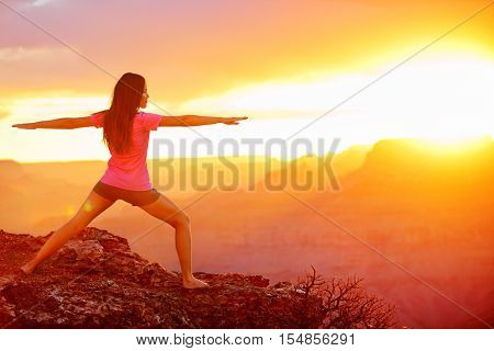 Yoga woman meditating at sunset in Grand Canyon. Female model meditating in serene harmony in warrior pose. Healthy wellness lifestyle image with multicultural young woman. From Grand Canyon, USA