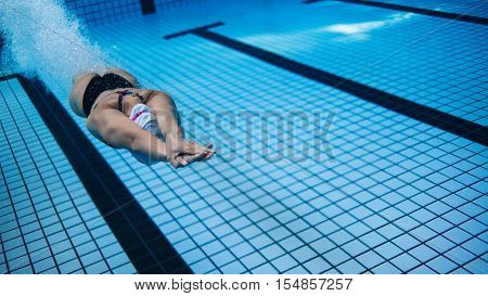 Underwater shot of woman training in swimming pool after dipping. Female swimmer in action inside swimming pool.