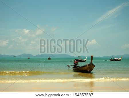 Big wood longtail boat and blue sea under cloudy sky