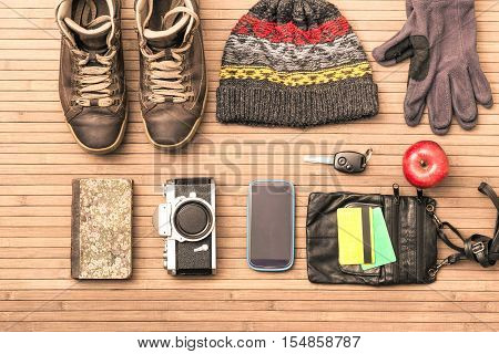 Winter season personal male belongings view from above - Essential clothing and objects for trekking excursion or short trip in cold days - Main focus on vintage camera
