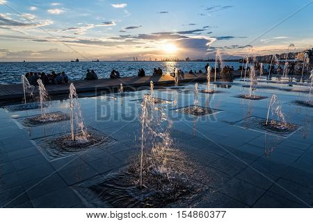 THESSALONIKI, GREECE - JUNE 14, 2016: People enjoy the sunset near the fountains at the sea front of the city on June 14, 2016 in Thessaloniki, Greece.