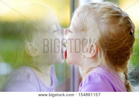 Funny Girl Licking Her Reflection On A Window