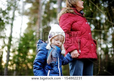 Little girl and her grandmother taking a walk on autumn forest