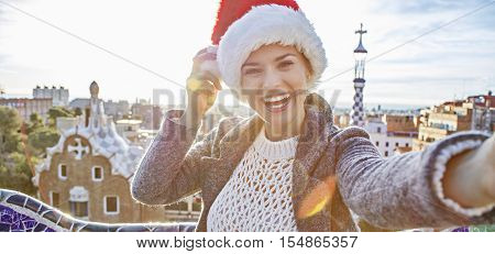 Smiling Traveller Woman In Santa Hat At Guell Park Taking Selfie