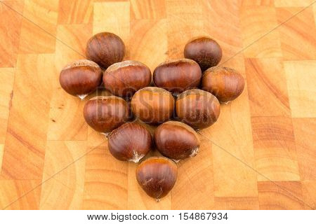 Autumn Seasonal Fruit Spanish Chestnuts On A Wooden Plate Formed To A Heart As A Symbol For The Word