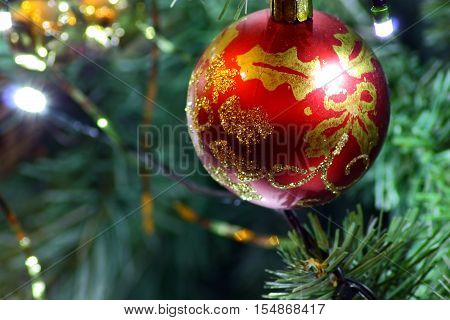 A red bauble with gold patterns hanging from a Christmas tree