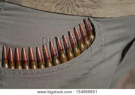 The bullets in the pocket of a woman in a row