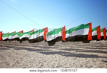 Lot of flags United Arab Emirates for the anniversary celebration on the beach. UAE Natoinal day. Emirates Flag. UAE celebrates National Day on 2nd December every year.