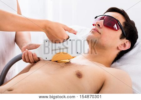 Therapist Giving Laser Epilation Treatment To Young Man In Spa