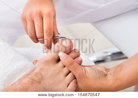 Close-up Of A Manicurist With Scissors Trimming Person's Toenail