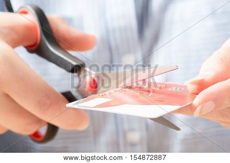 Hands Cutting Visa Card With Scissors