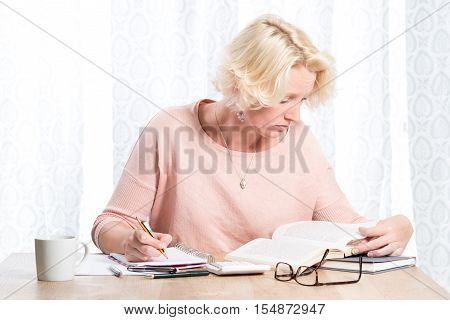 Woman Sitting At Wooden Table With Writing Pad And Books