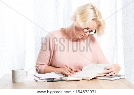 Woman In Glasses At Desk Holds Pen While Reading Books