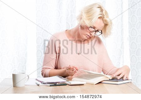 Woman In Glasses Holding Pen Turns Book Page