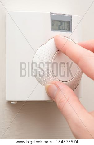 Hand Changing Room Temperature With Wall Mounted Thermostat