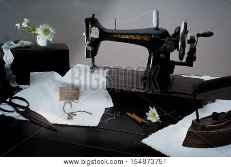 Classic retro style manual sewing machine ready for sewing work. The machine is old style made of metal with floral patterns