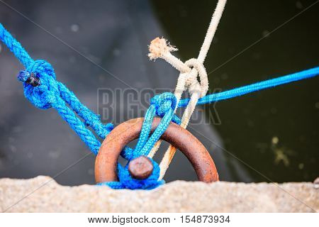 Dock ring trussed wrapped with mooring rope docking line hawser in harbor docks.