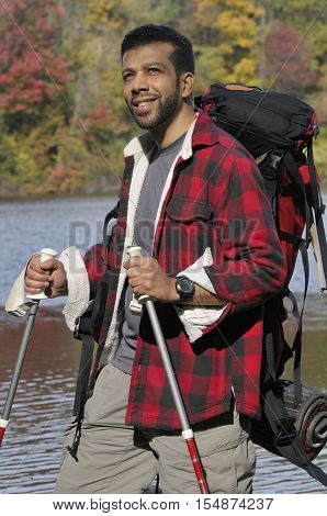 Hispanic man backpaking outdoors with trekking poles