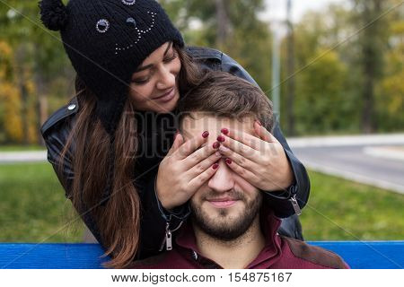 Closeup shot of young beautiful stylish couple in autumn park. She closes his eyes. He has a beard. She has a piercing in the nose. She wears black hat with bubo.