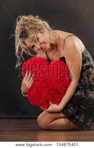 Woman mid aged blonde female wearing black evening dress holding big pillow in form of heart love symbol studio shot on black. Valentines day happiness concept