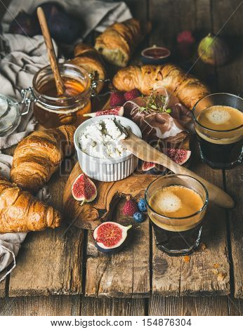 Breakfast with croissants, ricotta cheese, figs, fresh berries, prosciutto meat, honey in glass jar and two glasses of espresso coffee over rustic wooden background, selective focus