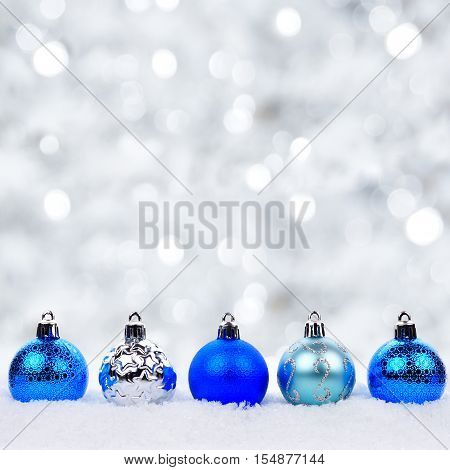 Blue And Silver Christmas Ornaments In Snow With Twinkling Silver Background