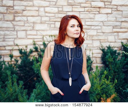 Closeup portrait of sexy middle aged white caucasian woman with waved curly red hair in black dress looking in camera outside in park beauty fashion lifestyle concept