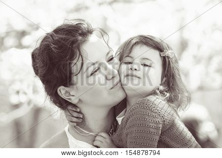 Black and white close up portrait of caucasian mother holding hugging cuddling her daughter smiling on sunny spring summer day in park outside Mothers day retro vintage style