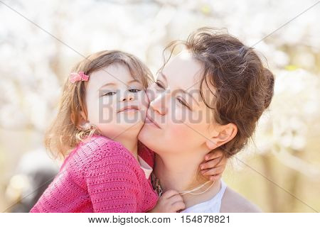 Close up portrait of caucasian mother in white dress holding hugging her daughter in pink clothes kissing her in cheek on sunny spring summer day in the park outside