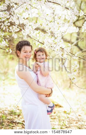 Portrait of caucasian pregnant mother in long white dress holding her daughter in pink clothes on a spring summer day in park outside among blooming cherry trees