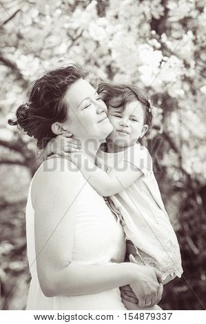 Black and white portrait of caucasian mother holding hugging cuddling her daughter smiling on sunny spring summer day in park outside Mothers day retro vintage style
