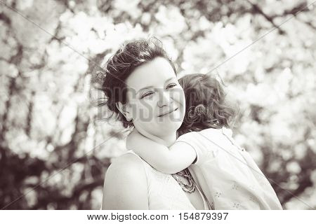 Black and white close up portrait of caucasian mother holding hugging cuddling her daughter smiling on sunny spring summer day in park outside Mothers day retro vintage style copyspace for text