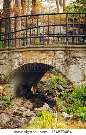 Small cute old stone bridge with archway in park with dried up river stream black metallic railings plants and trees around ancient old look