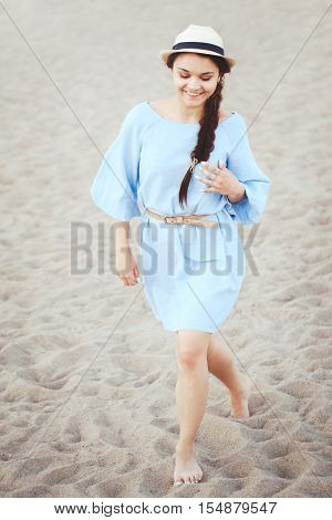 Portrait of smiling laughing white Caucasian brunette woman with tanned skin in blue dress and straw hat running on sand beach sunset on summer day lifestyle concept