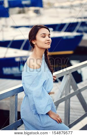 Portrait of white Caucasian brunette woman with tanned skin in blue dress by seashore lakeshore with yachts boats on background on water lifestyle concept