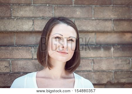 Close-up portrait of beautiful innocent Caucasian adult girl woman with long hair bob style hazel eyes in white tshirt standing behind brick wall outside looking away