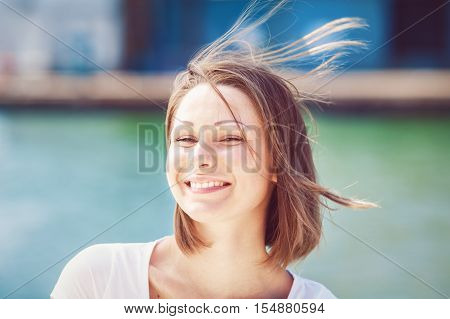 Closeup portrait of Caucasian woman girl in white tshirt looking in camera with messy long hair bob on sunny windy day outdoor bright high key hipster style