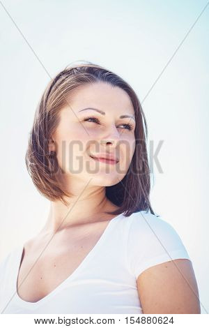 Closeup portrait of Caucasian woman girl in white tshirt looking away with messy long hair bob on sunny windy day outdoor bright high key hipster style
