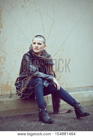 Portrait of beautiful Caucasian white young bald girl woman sitting on ground outside with shaved hair head in jacket scarf shaw jeans looking away toned with Instagram filters in blue green color