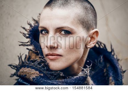 Closeup portrait of sad beautiful Caucasian white young bald girl woman with shaved hair head in leather jacket and scarf shawl spiritual mood state of mind