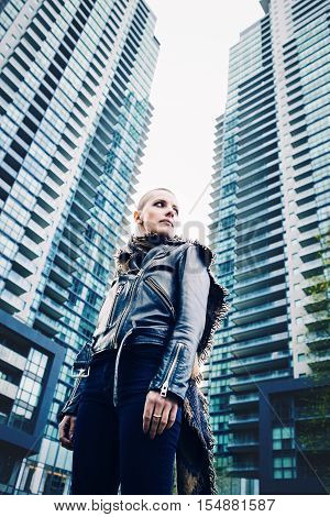 Wide angle low point of view portrait of beautiful Caucasian white young bald girl woman with shaved hair head in leather jacket and scarf looking away spiritual mood state of mind
