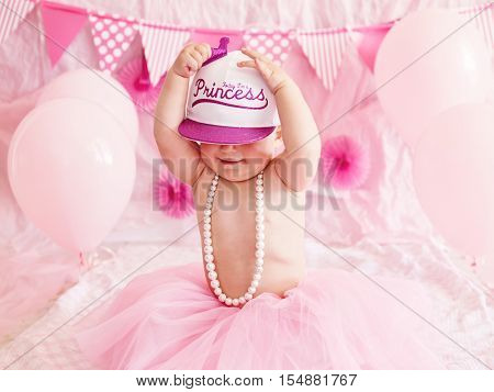 Portrait of cute adorable Caucasian baby girl with blue eyes in pink tutu skirt and pearls celebrating her first birthday with balloons looking away cake smash first year concept