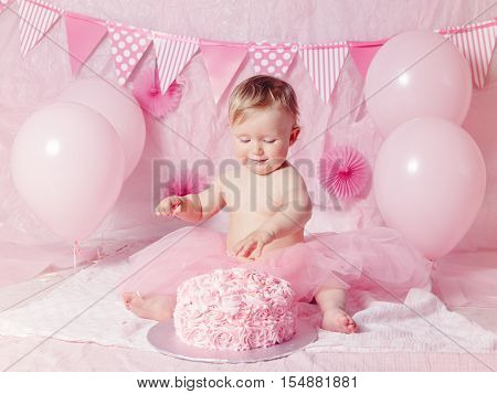 Portrait of cute adorable Caucasian baby girl with blue eyes in pink tutu skirt celebrating her first birthday with gourmet cake and balloons looking away cake smash first year concept