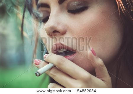Closeup portrait of white Caucasian beautiful young sexy brunette woman with closed eyes smoking cigarette toned with filters bad unhealthy habit lifestyle concept