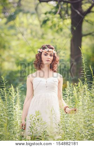 Beautiful white Caucasian girl with hazel eyes long wavy curly hair and flowers chaplet on head. Attractive young woman model in park outside country village hippie style